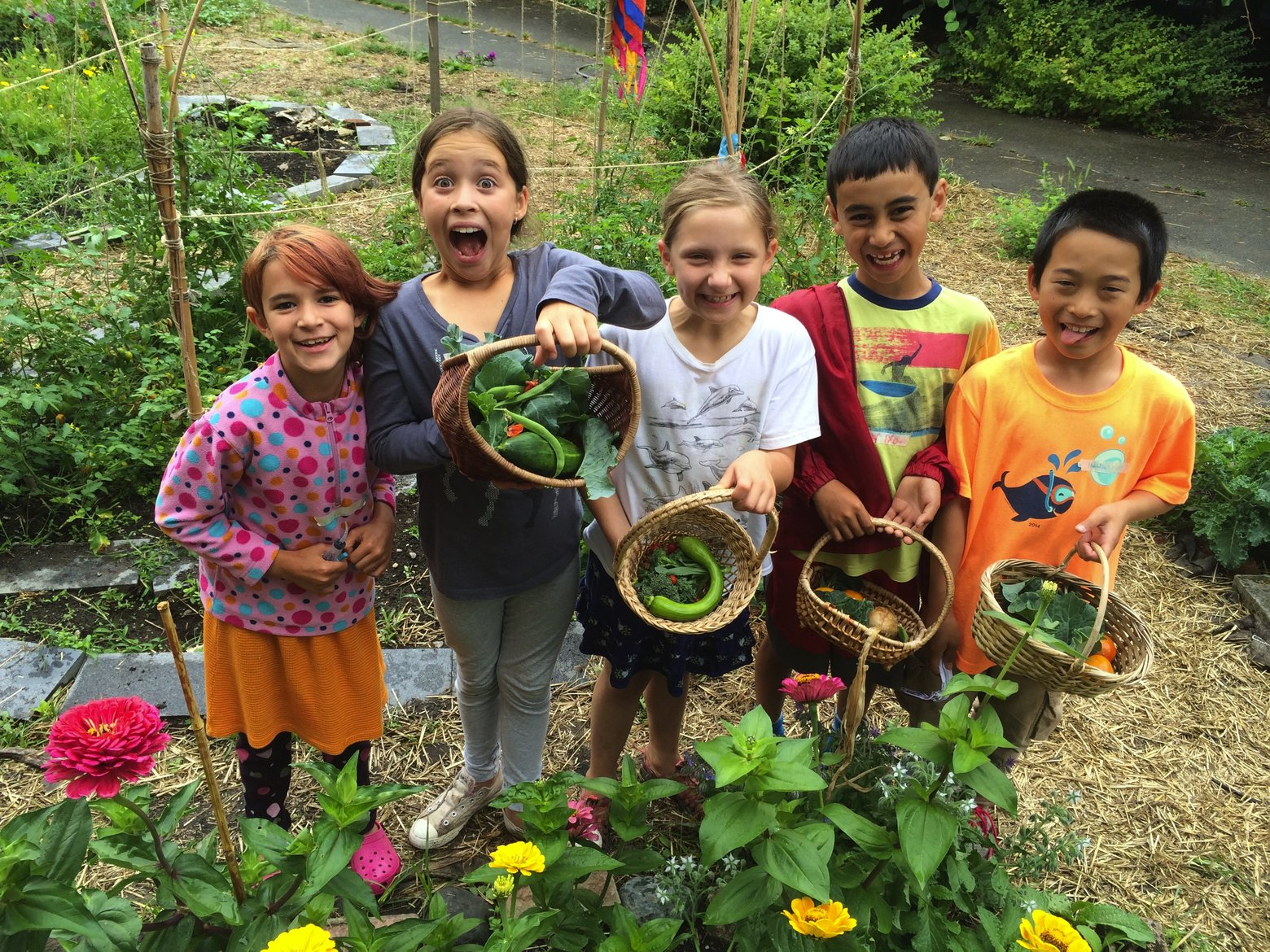 Photo of happy children holding baskets of vegetables